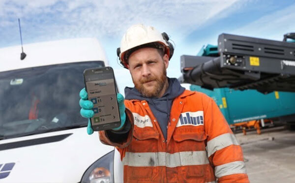 Blue group employee holding a phone running the JobWatch platform