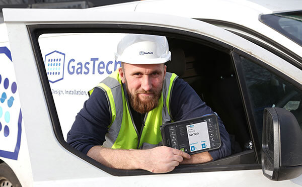 A GasTech engineer holding a BigChange JobWatch device