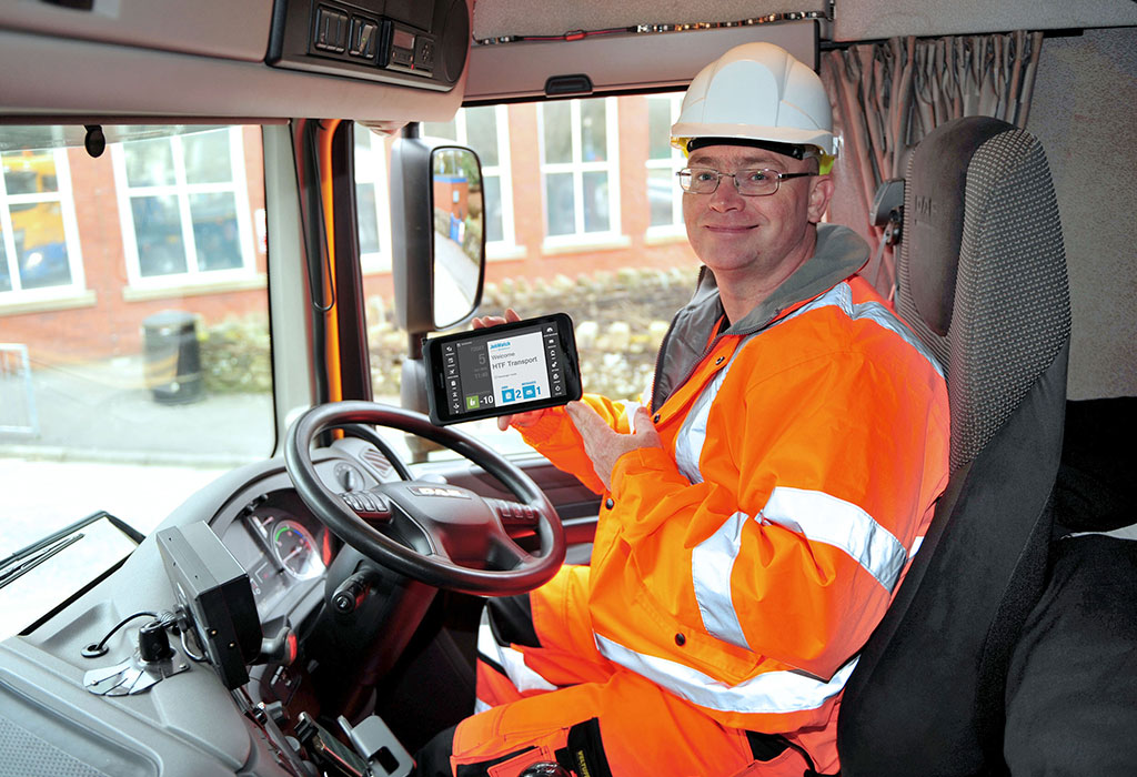 HTC Transport employee using a mobile BigChange device in his lorry.